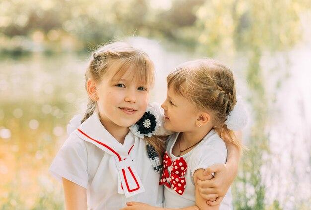 Duas irmãs se abraçam e se divertem no verão na natureza