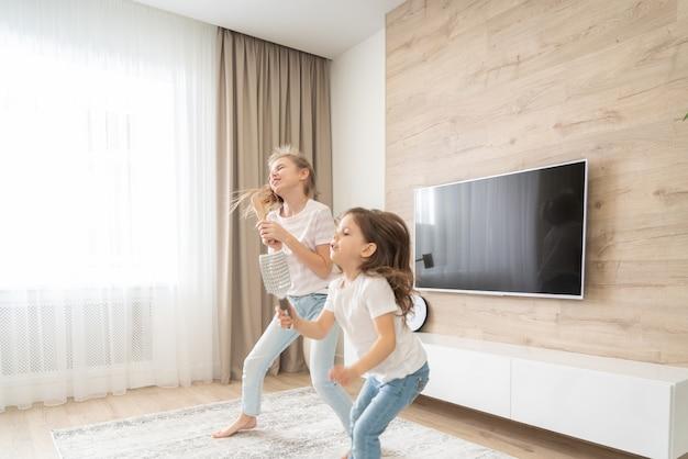 Duas irmãs se divertindo dançando na sala de estar e cantando karaokê