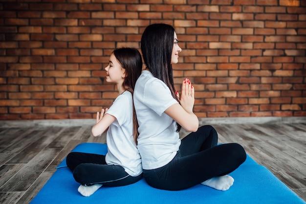 Duas irmãs sentadas costas com costas na academia e praticando ioga.