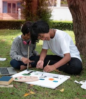 Duas irmãs sentadas na grama verde no andar térreo. pintar com cores na tela, com sentimento de felicidade, bom passatempo. atividade de fazer juntas