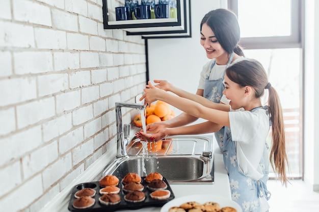 Duas irmãs sorridentes lavando as mãos na cozinha de casa