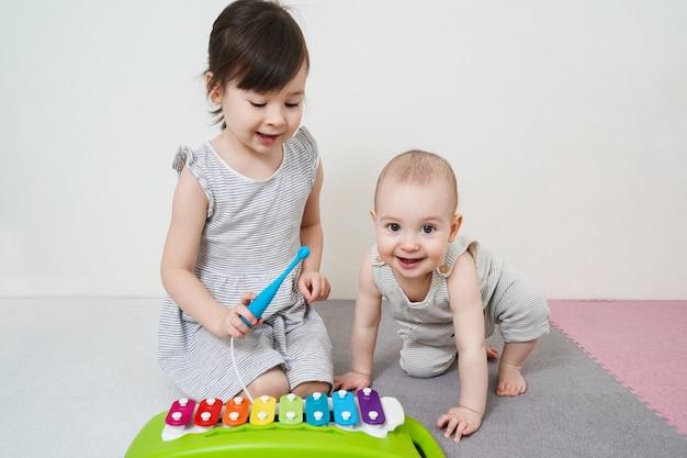 Duas irmãs tocam um xilofone. desenvolvimento precoce de crianças em idade pré-escolar.