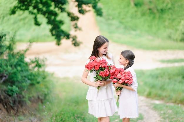 Duas irmãs, vestidas com vestidos brancos, se divertem no verão juntos. meninas estão segurando flores.
