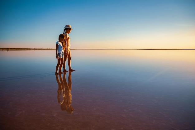 Duas irmãzinhas adoráveis e felizes estão caminhando ao longo do lago salgado rosa como um espelho, aproveitando o sol quente de verão nas tão esperadas férias