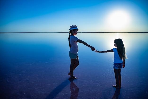 Duas irmãzinhas adoráveis e felizes estão caminhando ao longo do lago salgado rosa semelhante a um espelho, aproveitando o sol quente de verão nas tão esperadas férias