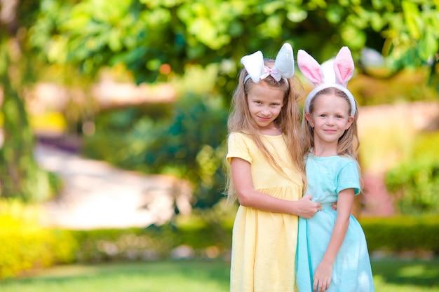Duas irmãzinhas adoráveis usando orelhas de coelho no dia da páscoa ao ar livre