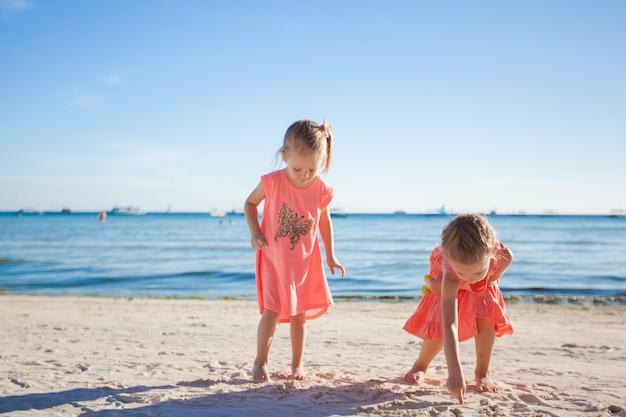 Duas irmãzinhas brincando juntos na praia branca