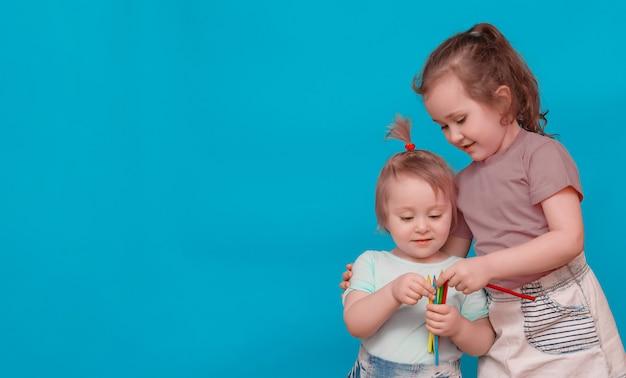 Duas irmãzinhas com lápis de cor juntas em um fundo azul