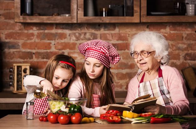 Duas irmãzinhas com vovó cozinhando juntos