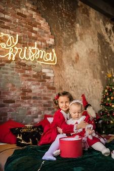 Duas irmãzinhas em vestidos de festa vermelhos sentam-se, abraçam-se na cama e brincam com as caixas da árvore de natal