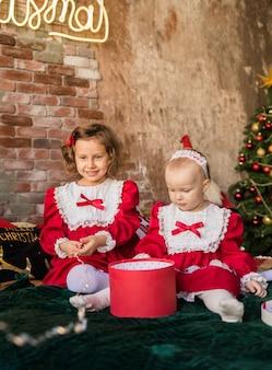 Duas irmãzinhas em vestidos de festa vermelhos sentam-se na cama e brincam com as caixas da árvore de natal