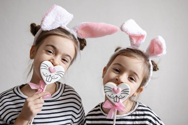 Duas irmãzinhas engraçadas estão posando com pão de mel de páscoa em forma de rostos de coelhinhos.