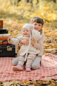 Duas irmãzinhas estão abraçando na praia durante um piquenique no parque. tempo de outono.
