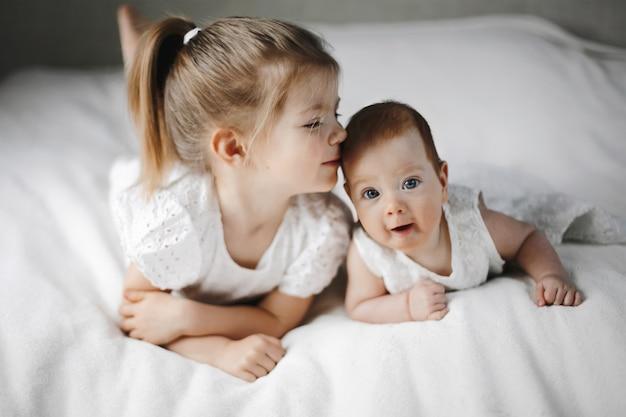 Duas irmãzinhas estão deitadas nas barrigas, vestidas com vestidos fofos brancos