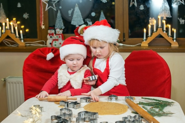 Duas irmãzinhas fofas cozinhando biscoitos de natal na aconchegante cozinha de casa