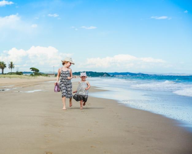Duas irmãzinhas fofos se divertindo em uma praia, mar mediterrâneo