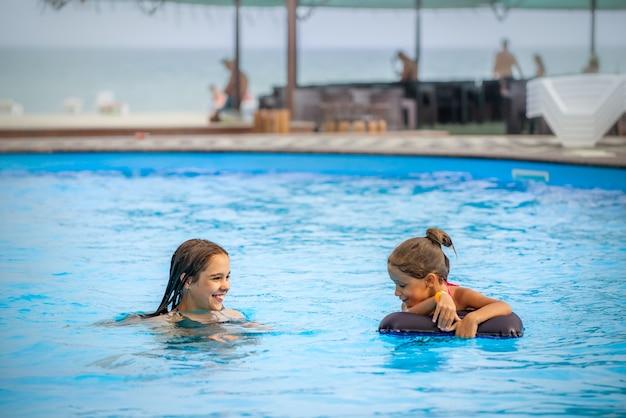 Duas irmãzinhas nadando e sorrindo em uma grande piscina