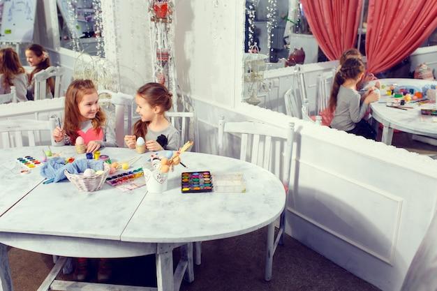 Duas irmãzinhas pintando ovos de páscoa coloridos em casa