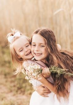 Duas irmãzinhas se abraçam e colhem flores no verão