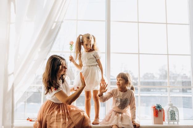 Duas irmãzinhas vestidas com os lindos vestidos e a jovem mãe sentada no parapeito da janela ao lado do espelho quando o inverno está lá fora.