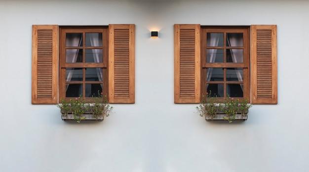 Duas janelas frontais modernas com parede branca vista de fora