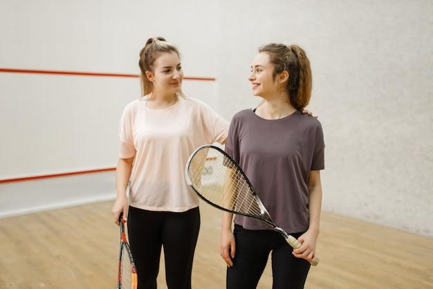 Duas jogadoras de squash posam no vestiário