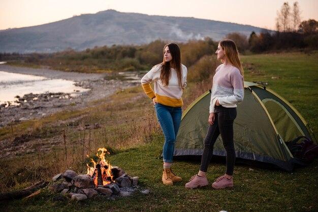 Duas jovens acampando ao ar livre perto da lareira