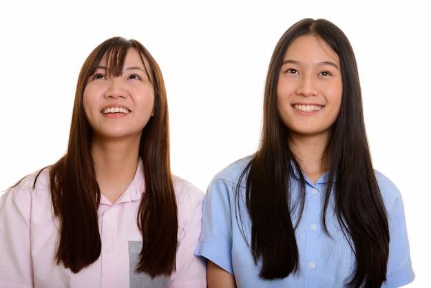 Duas jovens adolescentes asiáticas felizes sorrindo e pensando