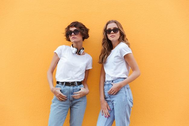 Duas jovens alegres adolescentes em óculos de sol posando