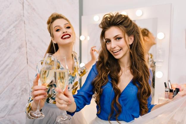 Duas jovens alegres com aparência luxuosa se divertindo em um salão de cabeleireiro