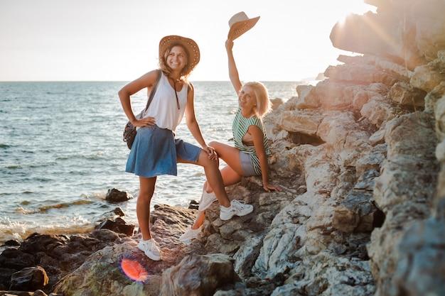 Duas jovens alegres em chapéus descolados em uma rocha na costa do mar. paisagem do verão com menina, mar, ilhas e luz solar laranja.