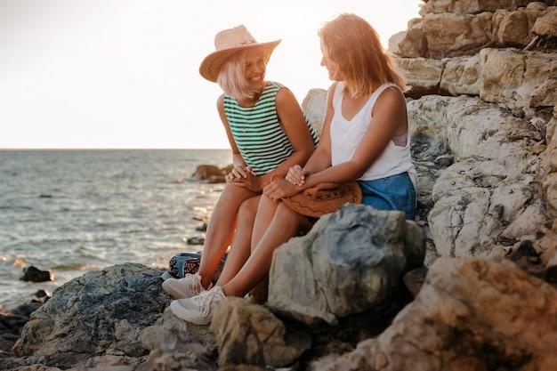 Duas jovens alegres em chapéus descolados na rocha na costa do mar. paisagem do verão com menina, mar, ilhas e luz solar laranja.