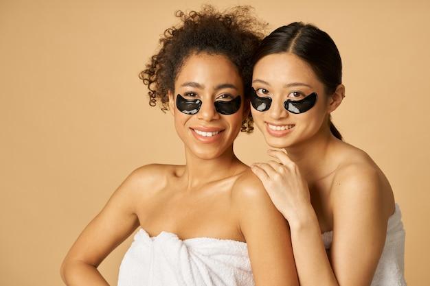 Duas jovens alegres enroladas em uma toalha branca posando com tapa-olho preto aplicado