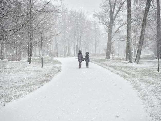 Duas jovens amigas andando no parque de inverno nevado.