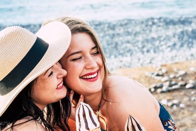 Duas jovens amigas brancas ficam juntas em atividades de lazer ao ar livre tomando sorvete