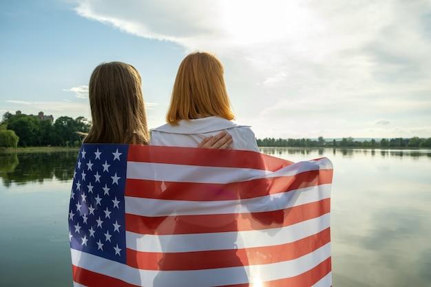 Duas jovens amigas com a bandeira nacional dos eua nos ombros