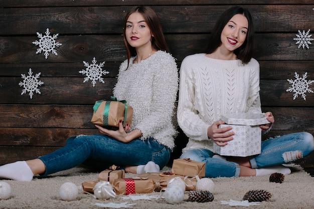 Duas jovens amigas engraçadas sorrindo e se divertindo, segurando presentes de natal