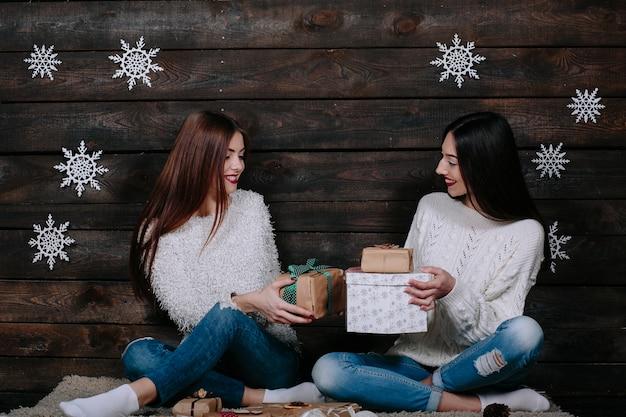 Duas jovens amigas engraçadas sorrindo e trocando presentes