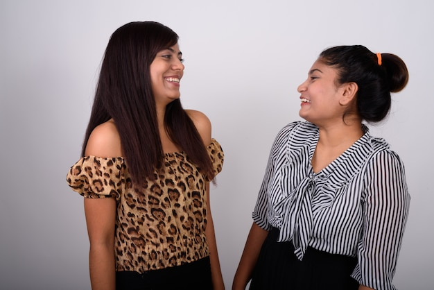 Duas jovens amigas felizes sorrindo e rindo enquanto se olham