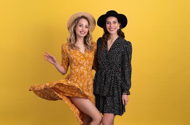 Duas jovens amigas lindas juntas isoladas em amarelo em um vestido preto e amarelo e um chapéu elegante tendência boho