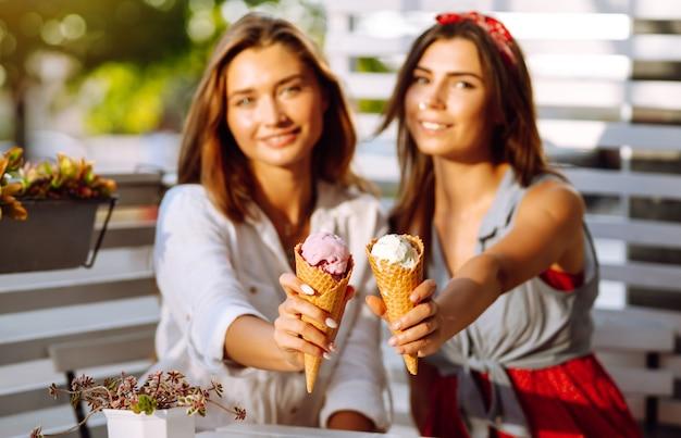 Duas jovens amigas se divertindo e tomando sorvete.