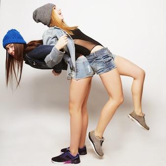 Duas jovens amigas se divertindo juntos. abraçando-se e sorrindo. estilo moderno.