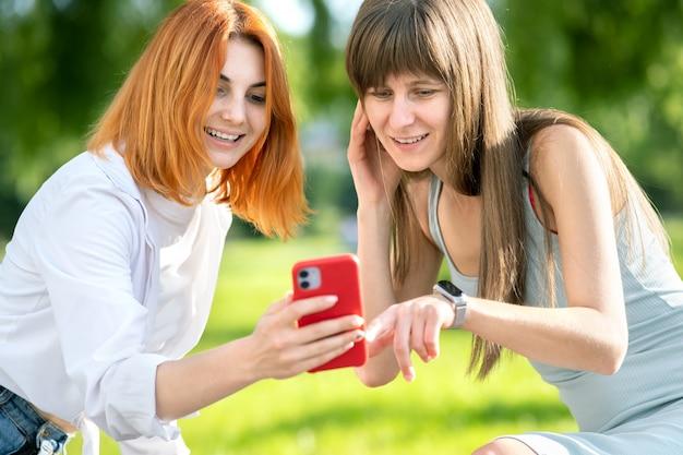 Duas jovens amigas sentadas em um banco no parque de verão, tomando uma selfie pela câmera do smartphone.