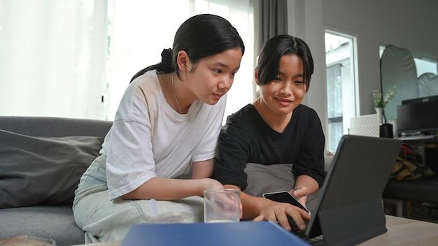 Duas jovens asiáticas usando o tablet do computador enquanto estão sentados juntos no sofá na sala de estar.