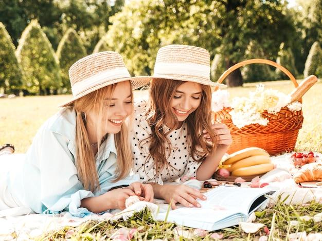 Duas jovens belas mulheres sorridentes no vestido de verão da moda e chapéus. mulheres despreocupadas fazendo piquenique do lado de fora.