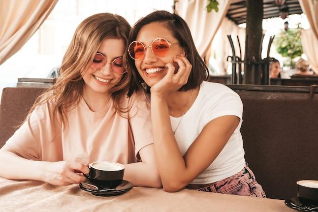 Duas jovens bonitas hipster garotas sorridentes em roupas casuais na moda verão. mulheres despreocupadas conversando no terraço varanda café e bebendo café. modelos positivos se divertindo e se comunicando