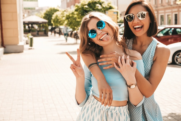 Duas jovens bonitas hipster garotas sorridentes em roupas da moda no verão. mulheres despreocupadas sexy posando na rua fundo em óculos de sol. modelos positivos, se divertindo e abraçando. mostrando o sinal de paz