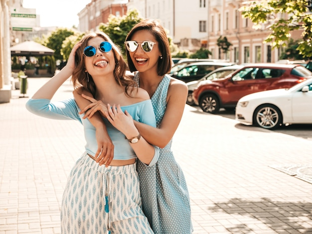 Duas jovens bonitas hipster garotas sorridentes em roupas da moda no verão. mulheres despreocupadas sexy posando na rua fundo em óculos de sol. modelos positivos se divertindo e abraçando