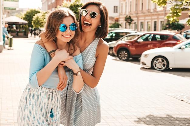 Duas jovens bonitas hipster garotas sorridentes em roupas da moda no verão. mulheres despreocupadas sexy posando no fundo da rua em óculos de sol. modelos positivos se divertindo e abraçando.
