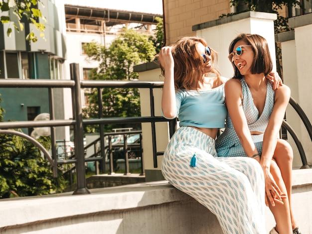Duas jovens bonitas hipster garotas sorridentes em roupas da moda no verão. mulheres despreocupadas sexy posando no fundo da rua em óculos de sol. modelos positivos se divertindo e enlouquecendo